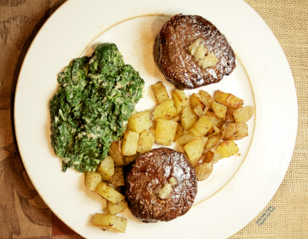 Two Reverse-Sear Filet Mignon Steaks on a platter with roasted potatoes and creamed spinach