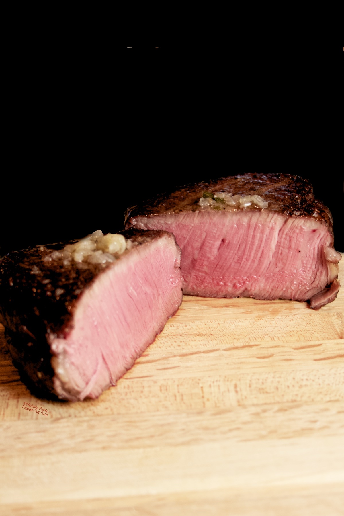 Reverse-Sear Filet Mignon Steak: a side view of one steak cut in half to show the perfect medium-rare interior.