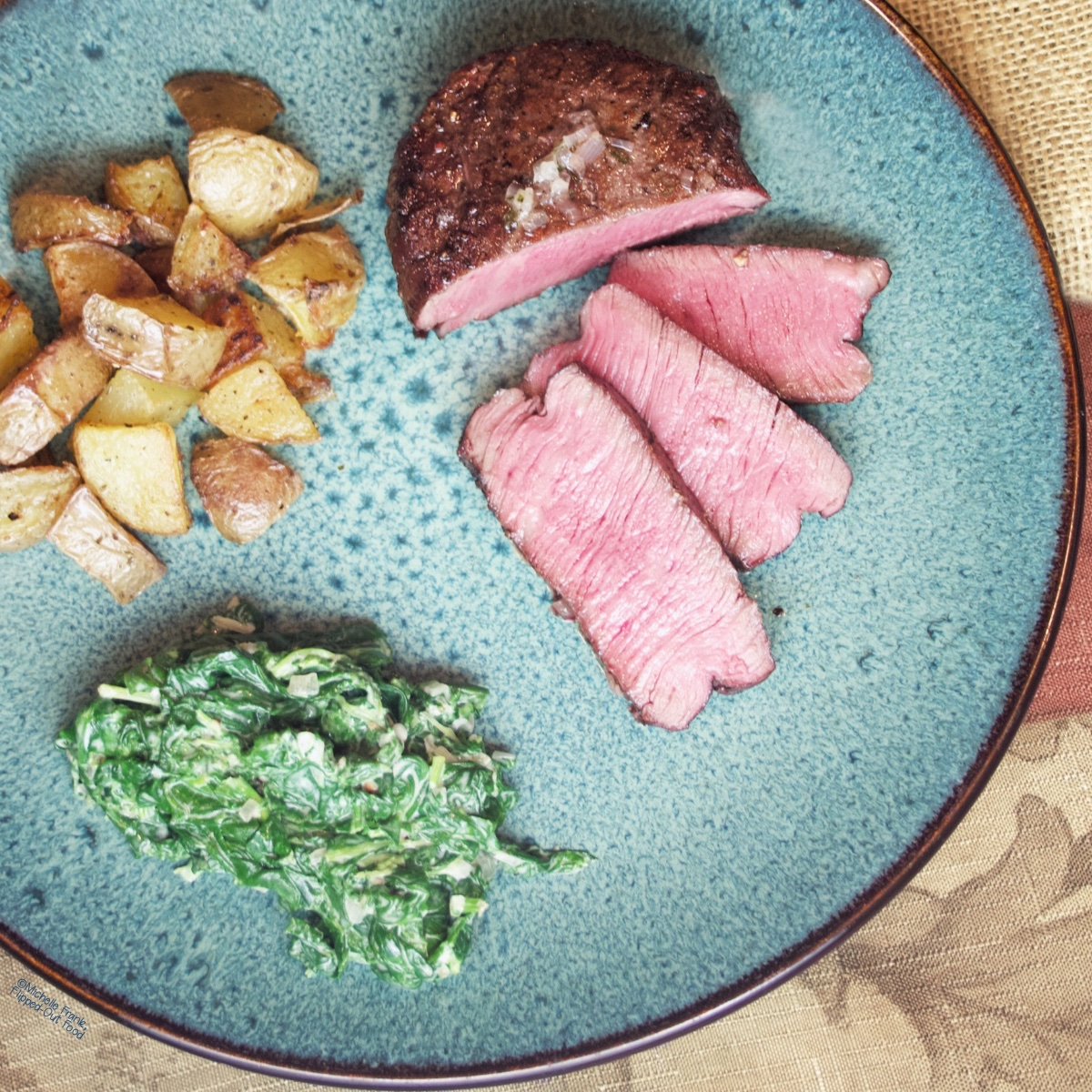 Reverse-Sear Fliet Mignon Steak on a blue plate with roasted potatoes and creamed spinach. Three slices have been cut from the juicy filet, which is cooked medium rare, and are fanned out on the plate.