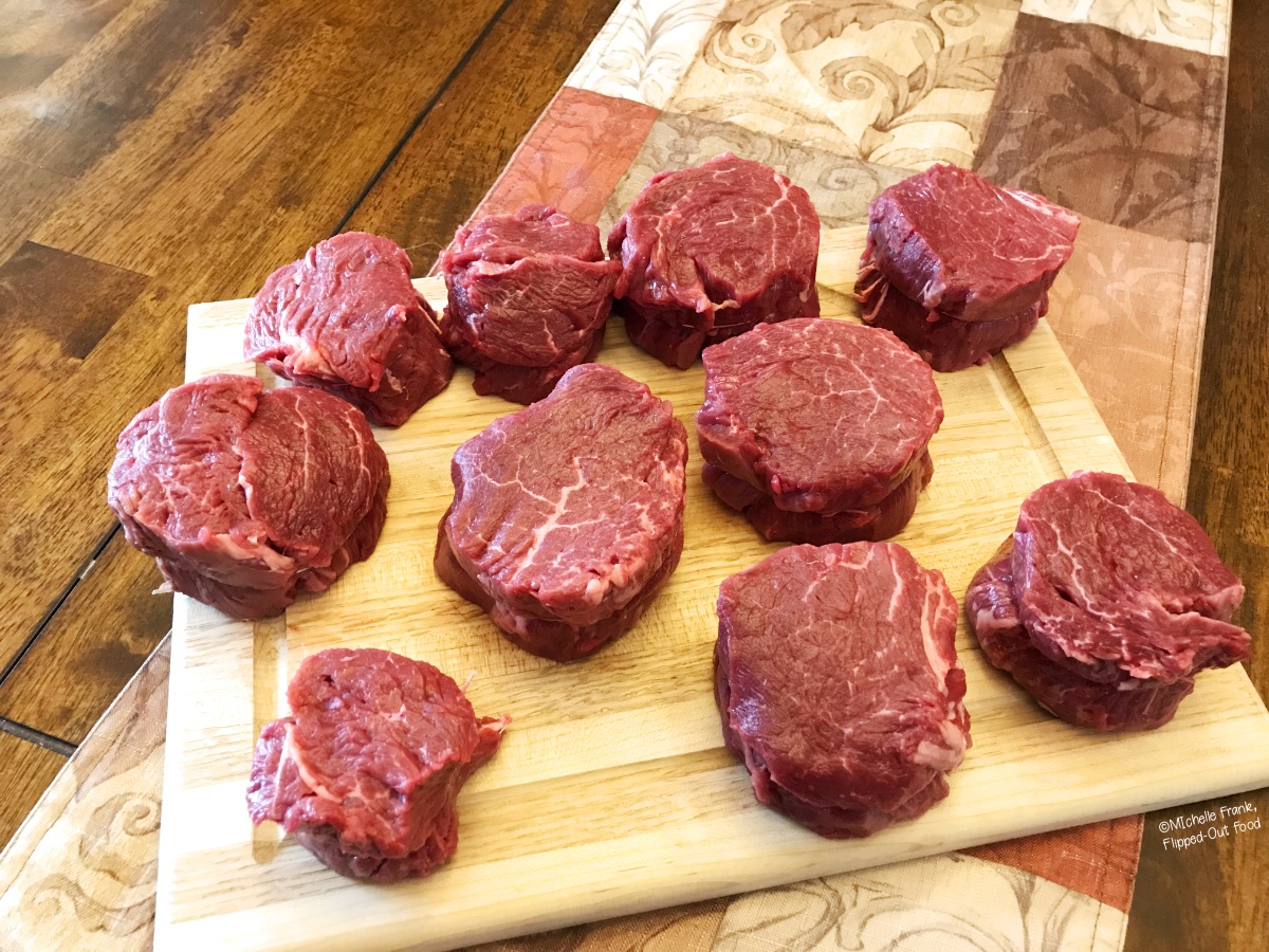 A whole beef tenderloin sliced into thick filet mignon steaks, all arranged on a cutting board.
