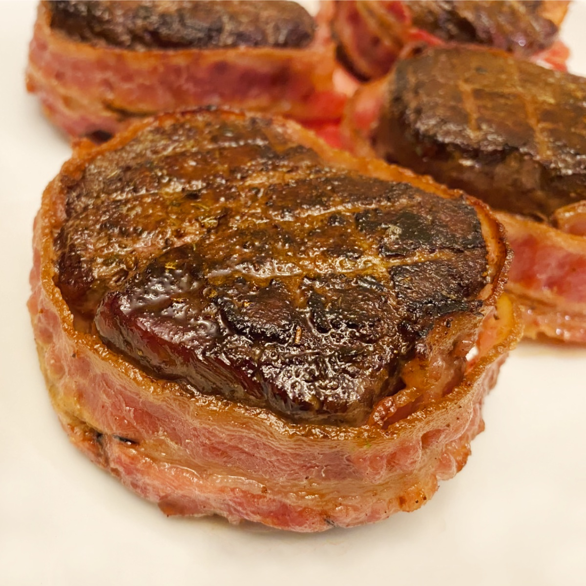 Close up view of reverse seared Filet Mignon bacon-wrapped steaks sitting on a white plate.