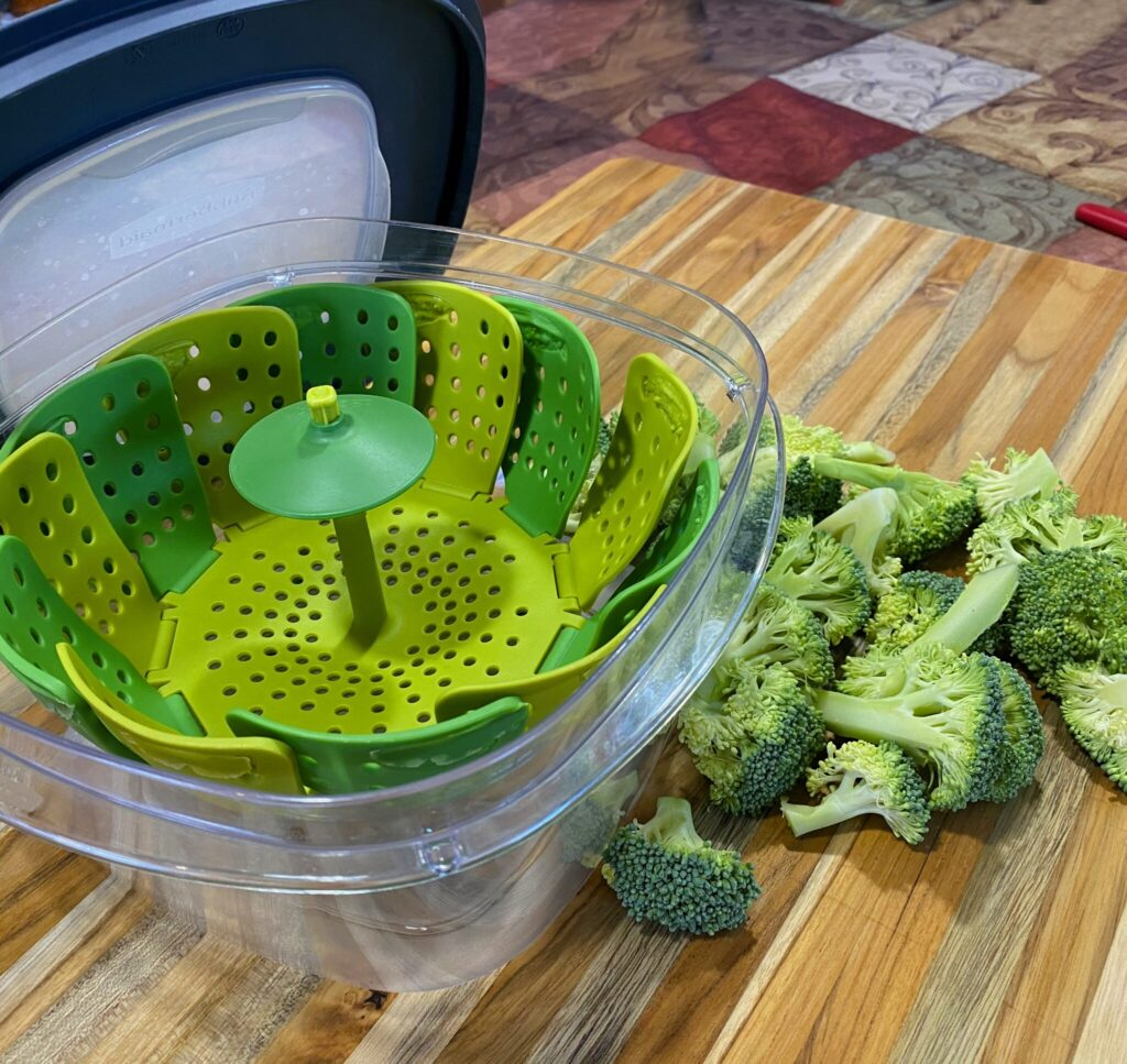Easy Microwave Broccoli steamer setup: a microwave-safe container with a lid, a silicone colander set inside, and an inch of water added to the bottom.