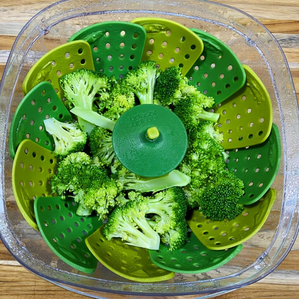 Easy Microwave Broccoli in the colander after being microwaved about 3 minutes. The color is beautiful, vibrant green and the broccoli is perfectly crisp-tender.