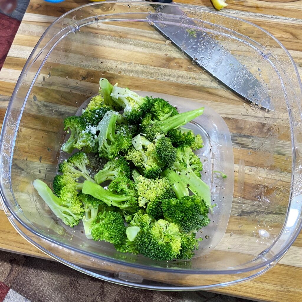 The cooked microwave broccoli in a bowl with Parmesan cheese, salt, pepper, and lemon juice, ready to be tossed together.
