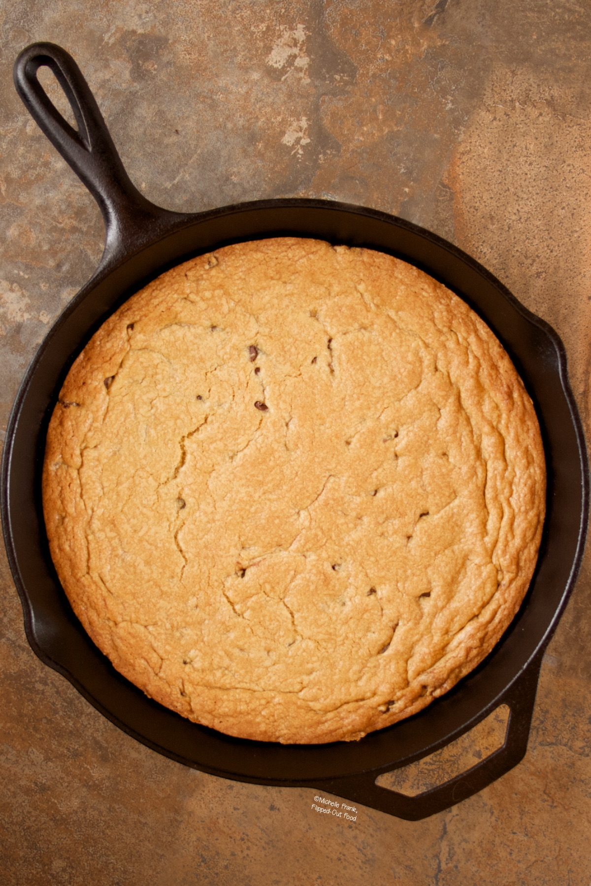 A golden-brown Cast Iron Chocolate Chip Cookie, fresh from the oven and still in its skillet.