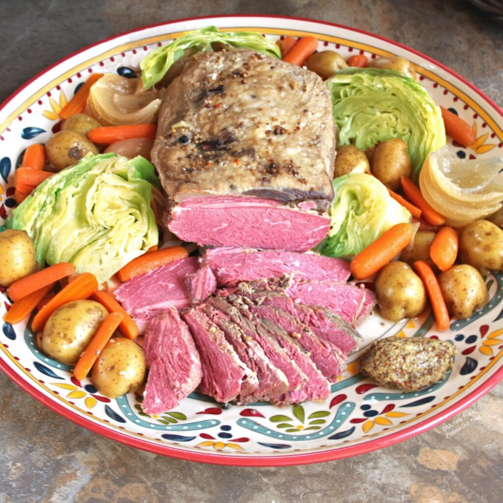 make-ahead crockpot corned beef and cabbage with potatoes and carrots on a large, decorative platter.