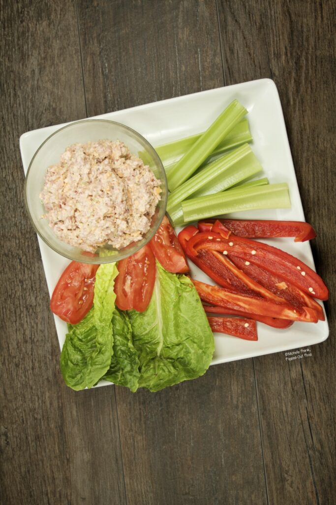 Keto Ham Salad Spread in a serving bowl set onto a plate with celery sticks, red pepper strips, Romaine lettuce, and tomatoes.