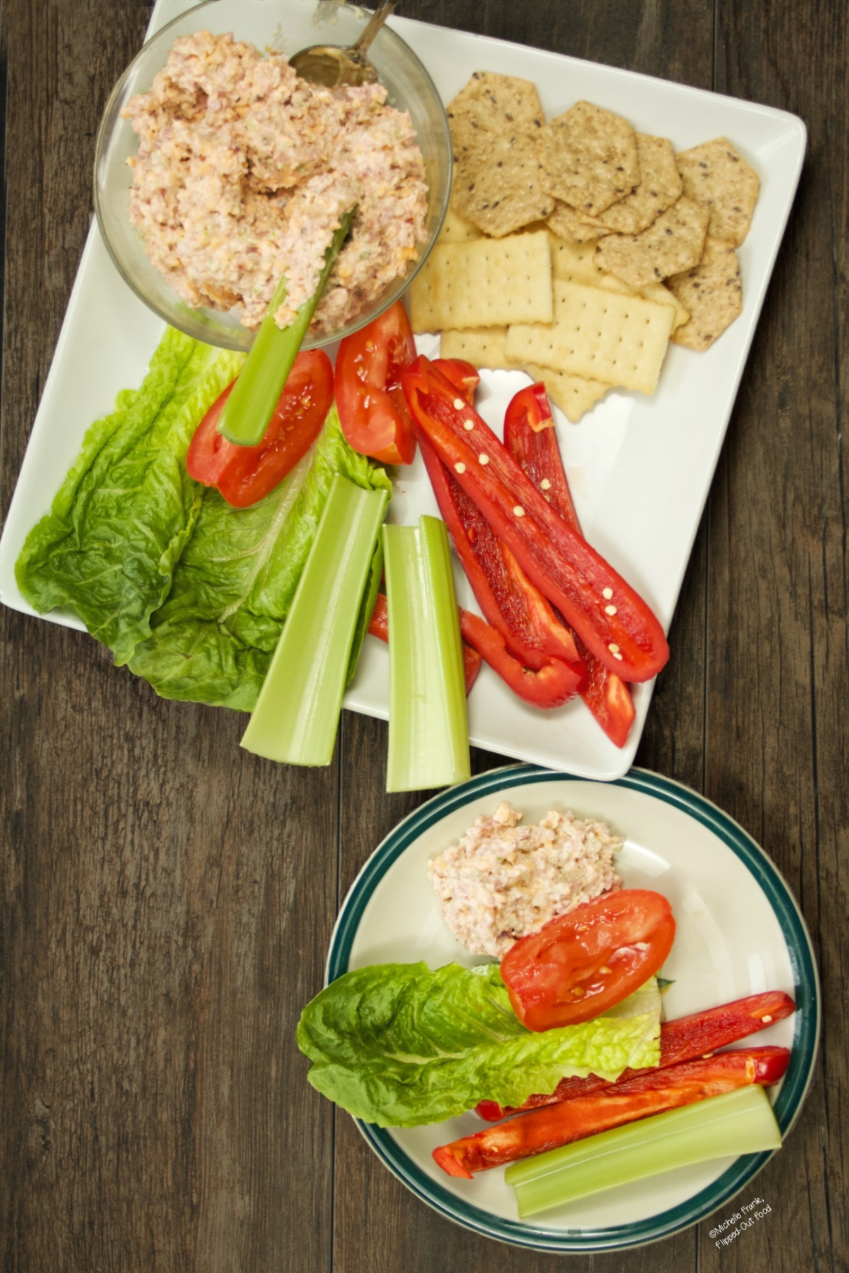 Keto Ham Salad Spread in a serving bowl set onto a white serving platter. The platter is full of crackers, sliced vegetables, and lettuce leaves. A small party plate loaded up with vegetables, lettuce, and the ham spread sits next to the platter.