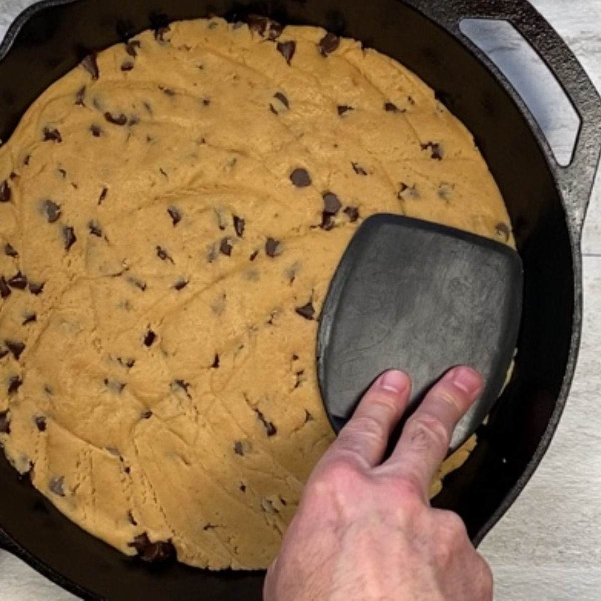 Overhead image showing how to use the underside of a spatula to press the raw cookie dough to an even thickness in the cast iron skillet.