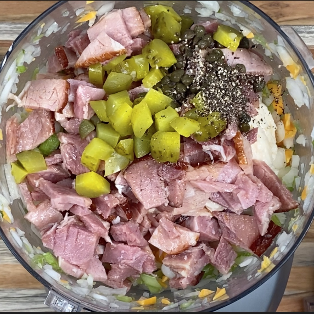 Overhead view of ham, pickles, capers, salt, pepper, mayonnaise, and mustard added to the food processor to finish the Keto Ham Salad Spread.