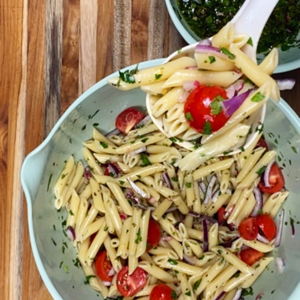 A serving spoon of chimichurri pasta salad being raised toward the camera, with the mixing bowl full of pasta salad underneath.