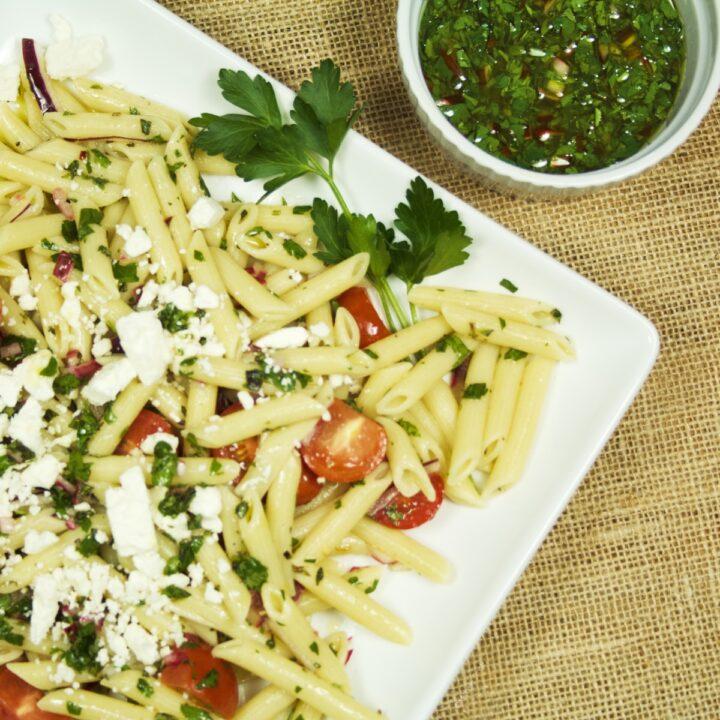Closeup of a platter full of Chimichurri Pasta Salad sitting next to a ramekin of chimichurri sauce.