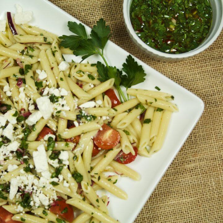 Chimichurri Pasta Salad on a white platter, sitting next to a ramekin of chimichurri sauce.
