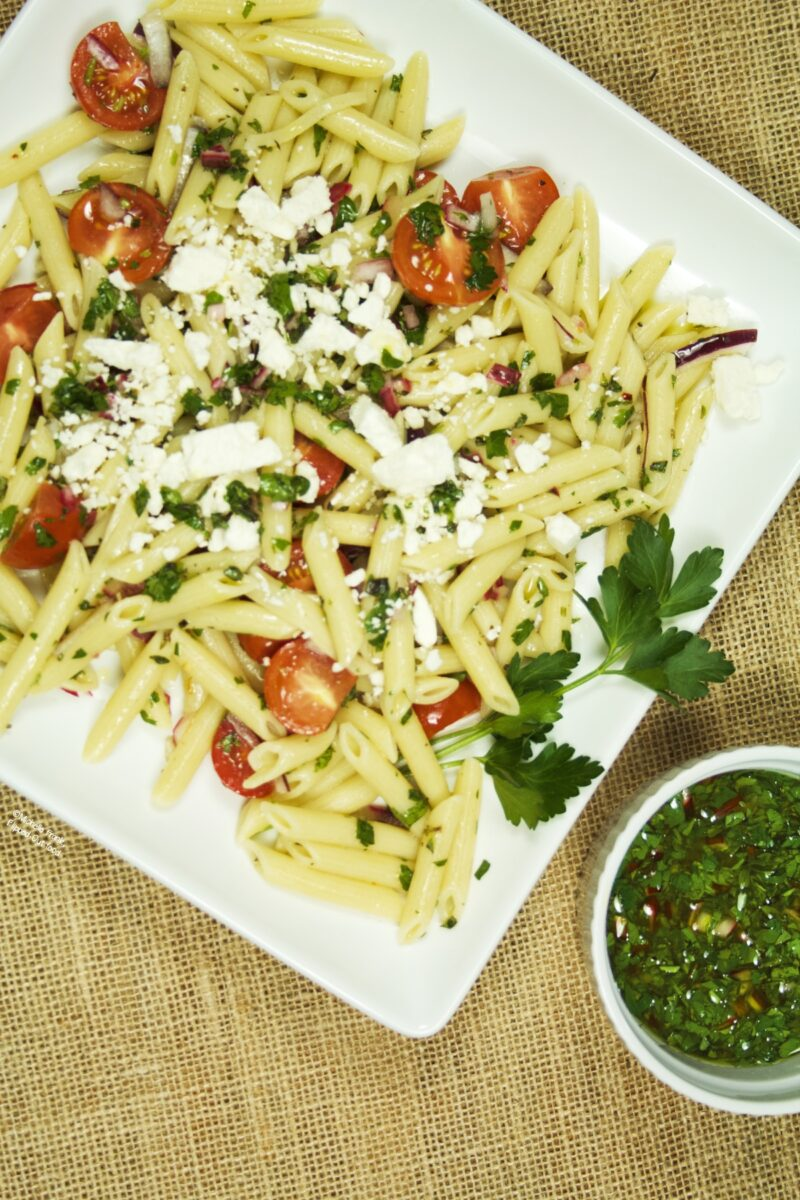 A plate of chimichurri pasta salad, garnished with feta cheese and a parsley sprig, sitting next to a ramekin of chimichurri sauce.