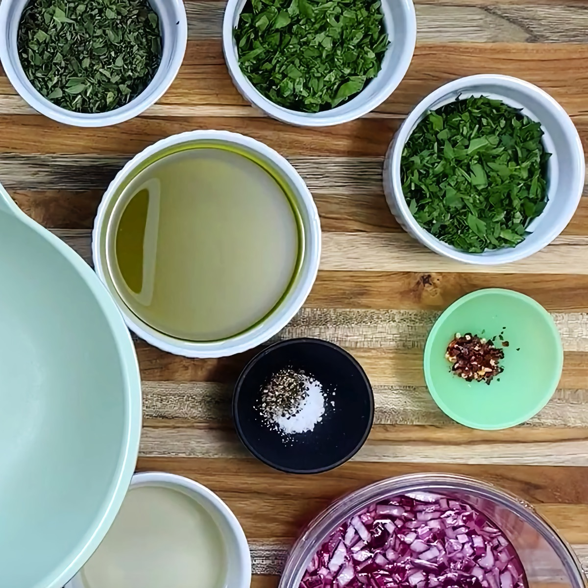 Ingredients for the chimichurri sauce. Clockwise from top left: oregano, parsley, cilantro, red pepper flake, pickled red onion, rice vinegar, salt and pepper, extra virgin olive oil.