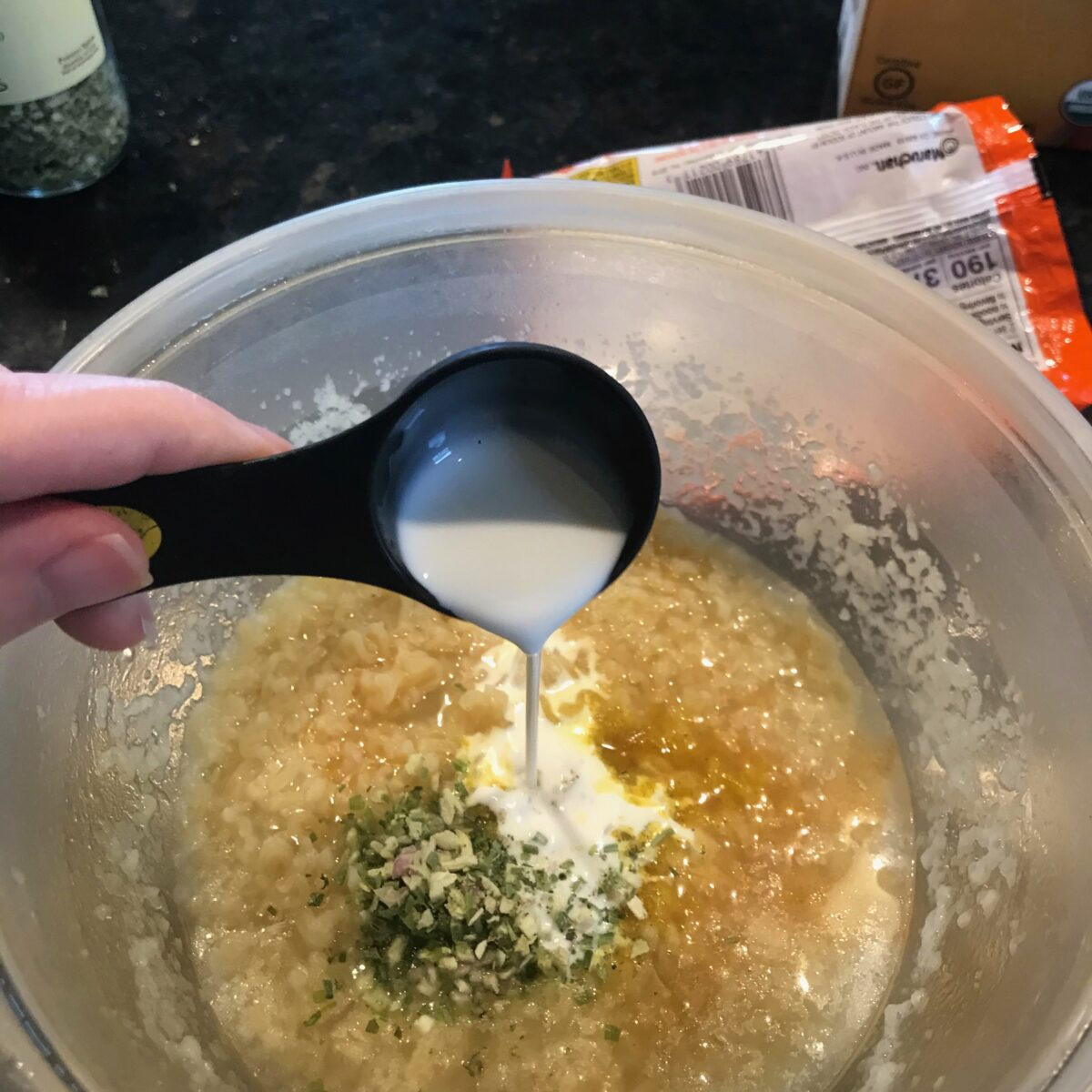 Top view showing the addition of cream and chicken broth to the cooked ramen noodles.