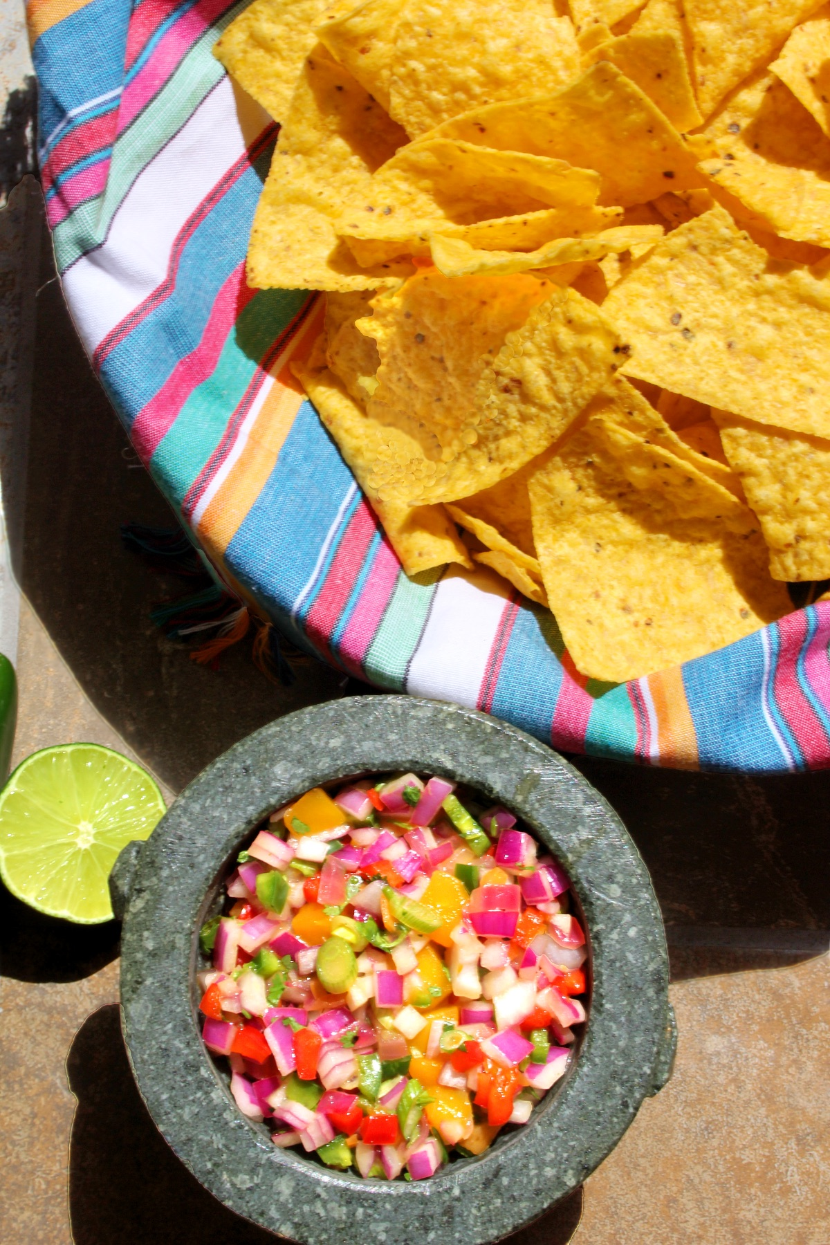 Fiery Mango-Habanero Salsa in a molcajete with tortilla chips and lime.