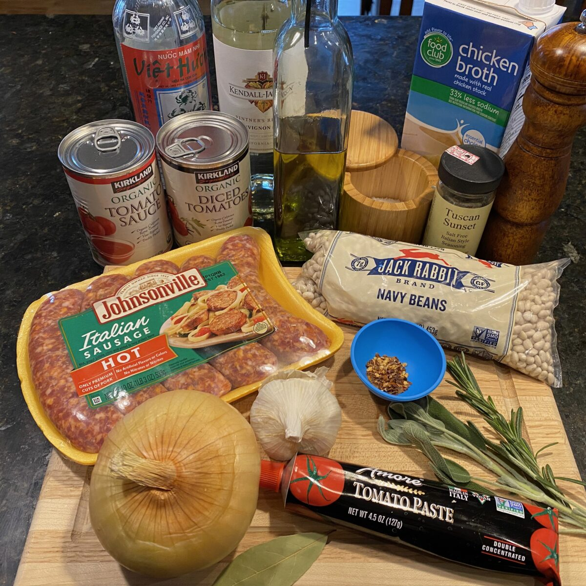 Ingredients for Italian Sausage and Beans: tomato sauce, diced tomatoes, fish sauce, white wine, olive oil, salt, chicken broth, dried Italian herbs, black pepper, navy beans, rosemary, sage, red pepper flakes, tomato paste, garlic, bay leaf, yellow onion, and Italian sausages.