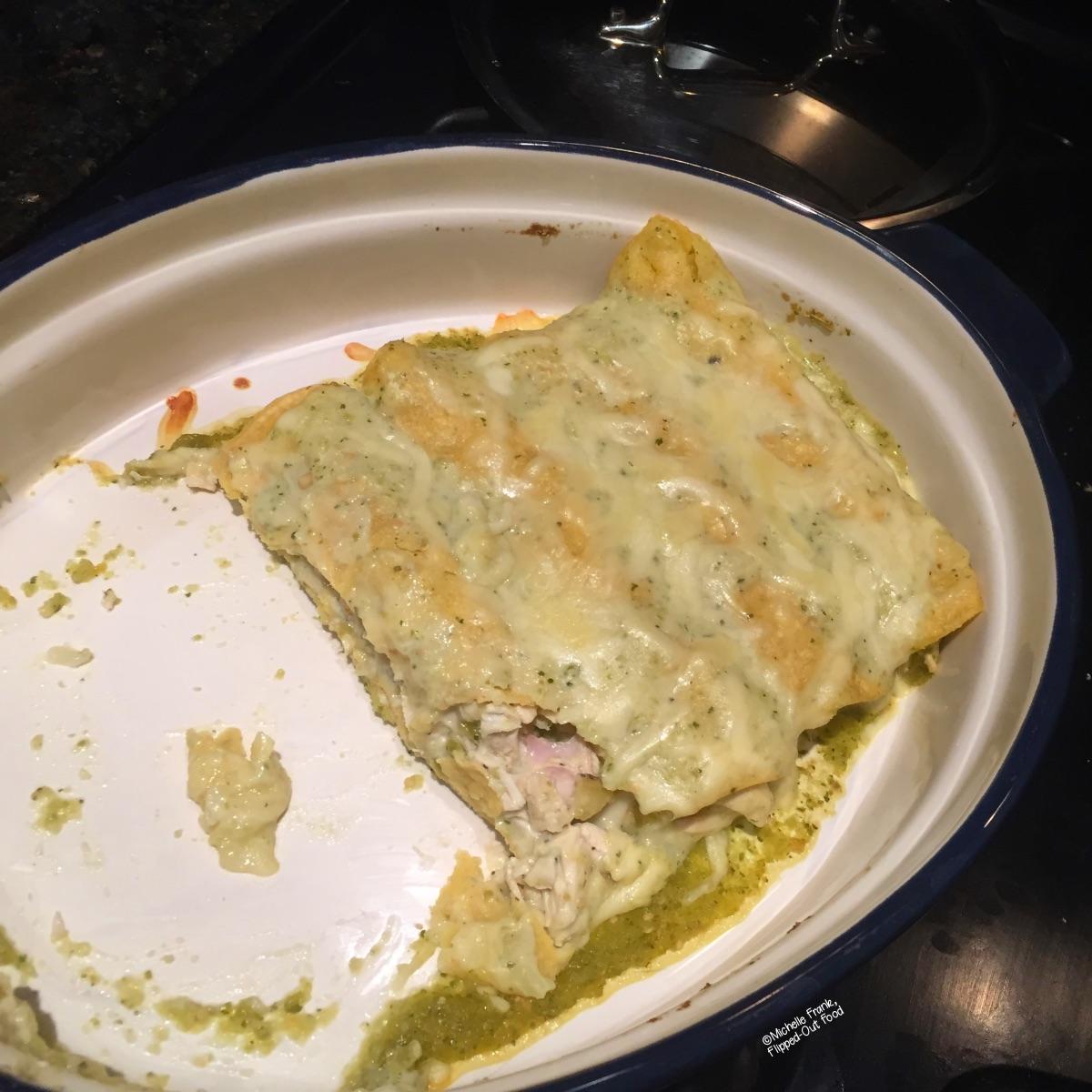 Half-eaten green chile turkey enchiladas in a baking dish.