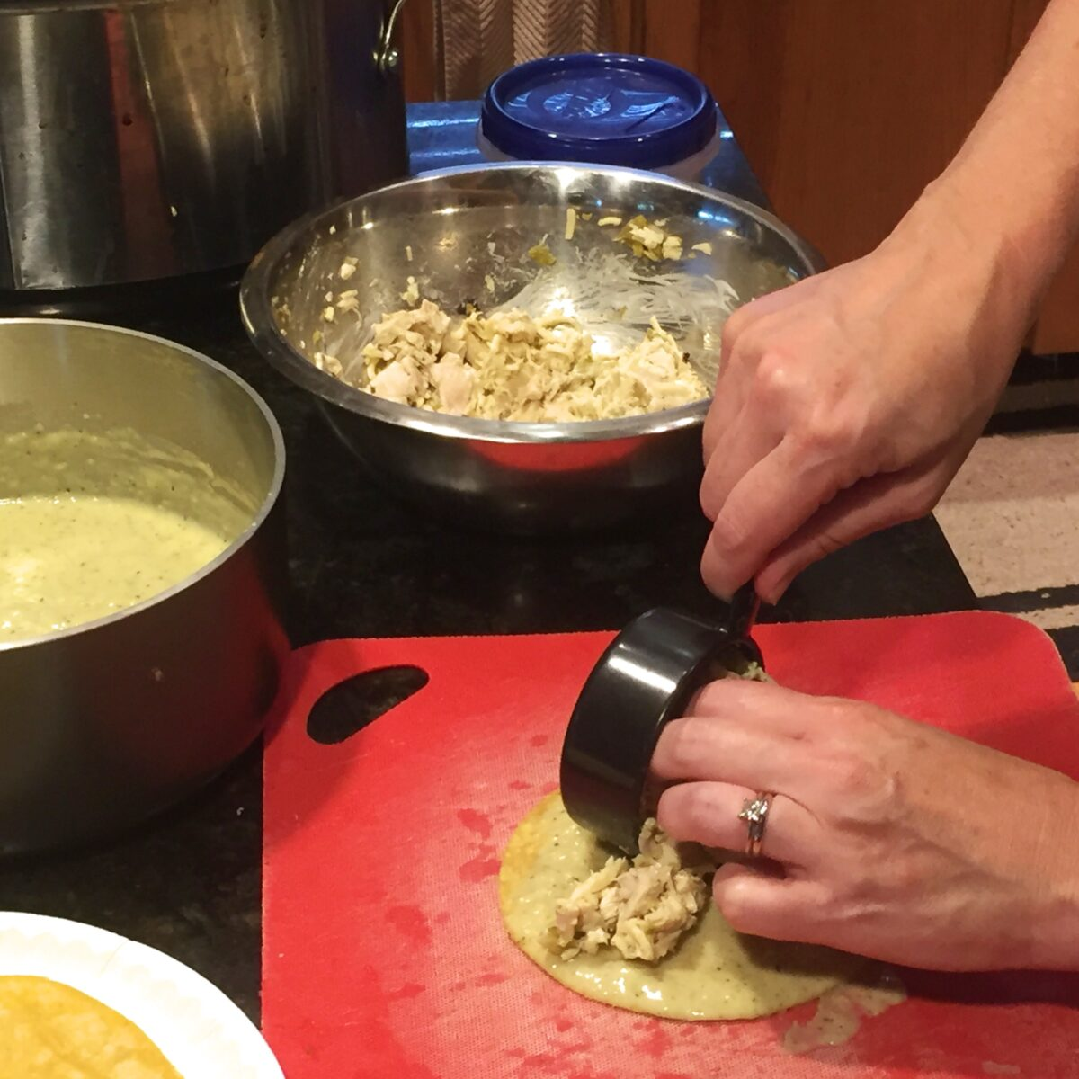 Adding enchilada filling to the sauce tortilla, ready for rolling.