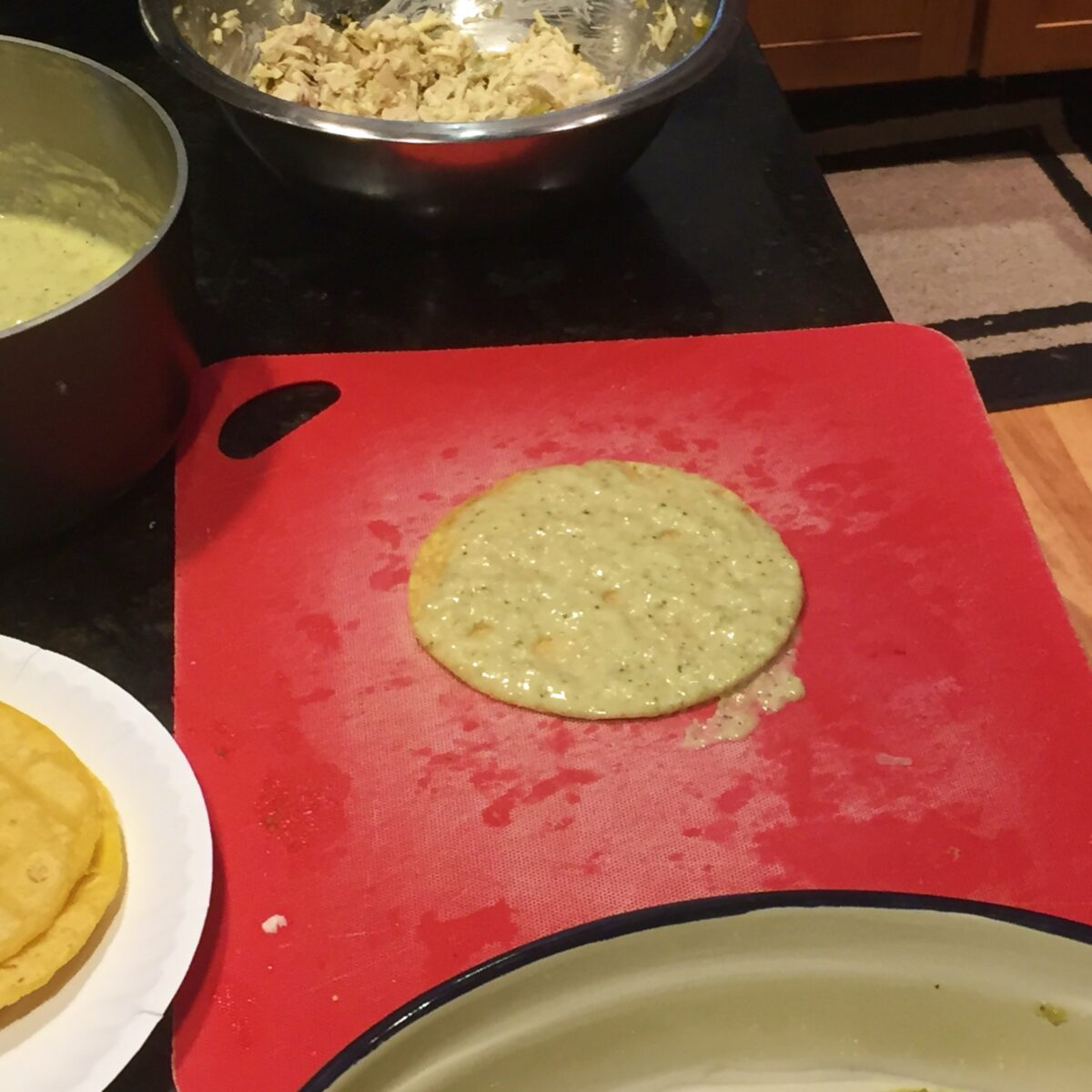 A corn tortilla with one side covered in creamy green chile enchilada sauce on a cutting board, ready for adding enchilada filling.