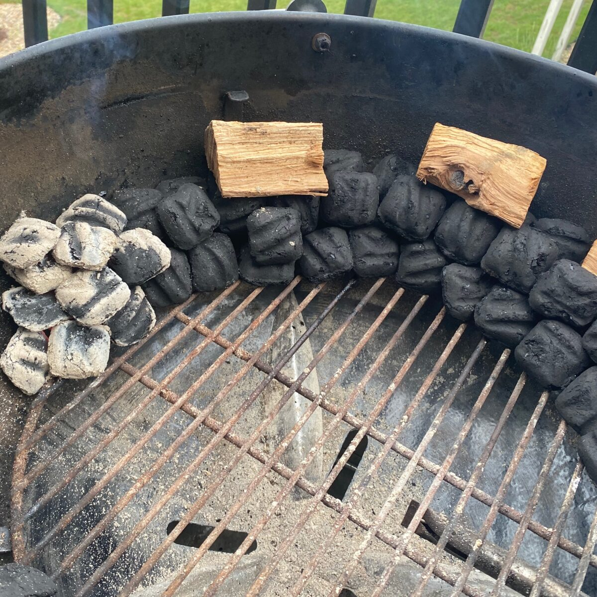 Close up view of the proper charcoal and wood set up to smoke on a charcoal grill.