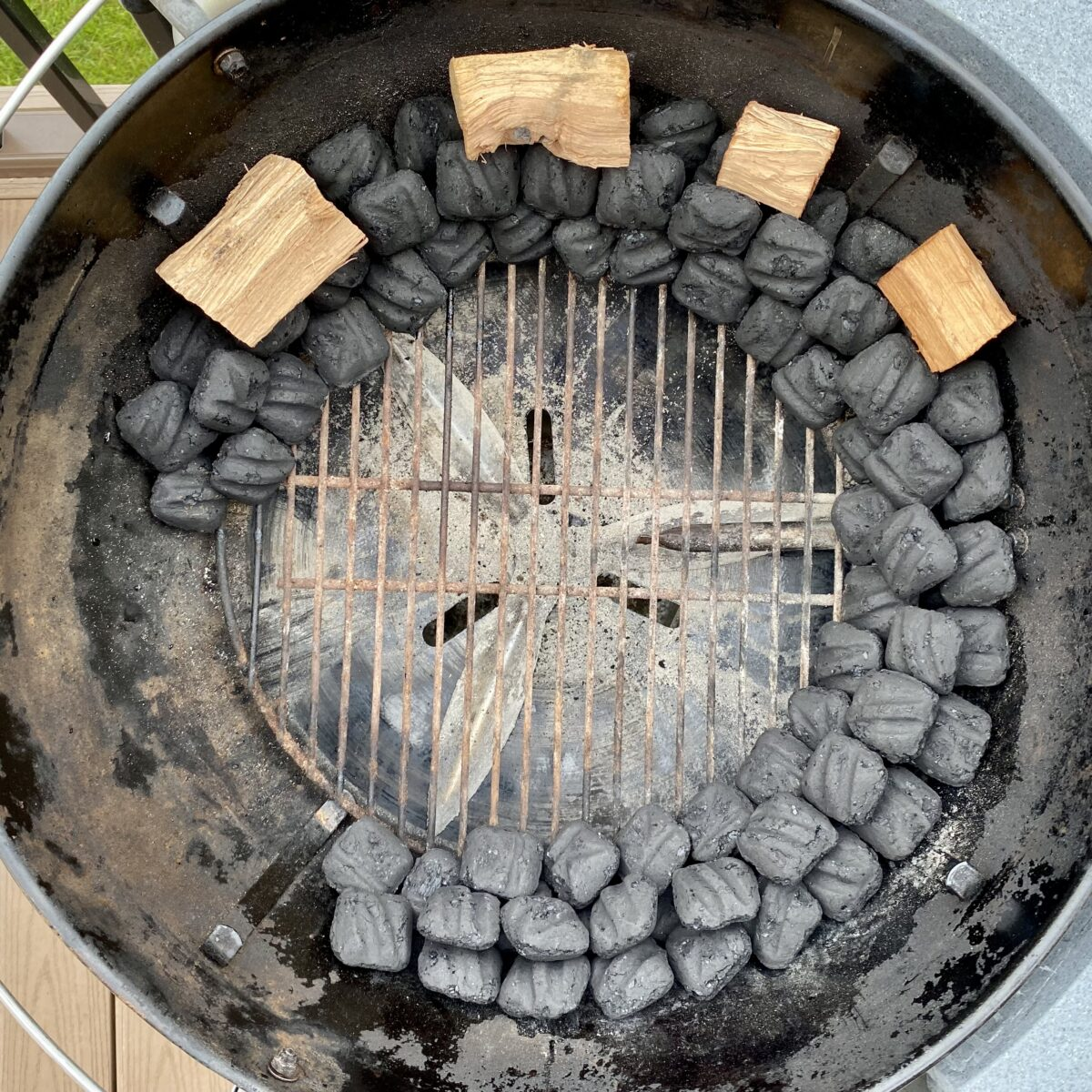 Overhead view showing four smoke wood chunks placed on the snake of unlit coals around the charcoal chamber.  Wood chunks cover about half the length of the snake of coals.