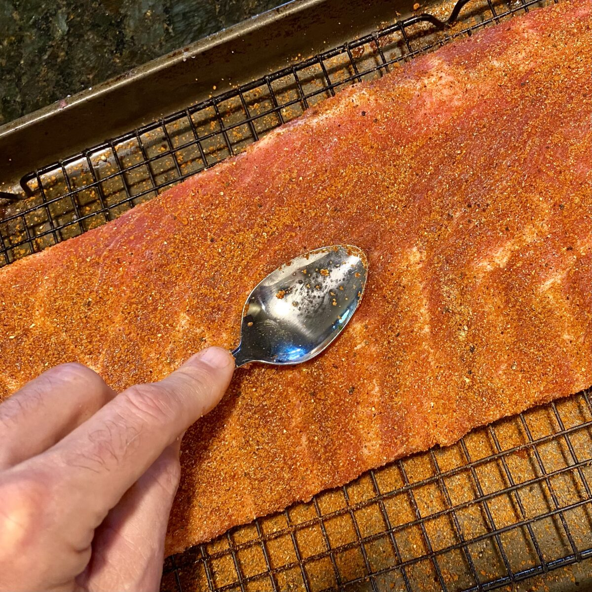 Top view showing how to use the back of a spoon to work the rib rub into the ribs.