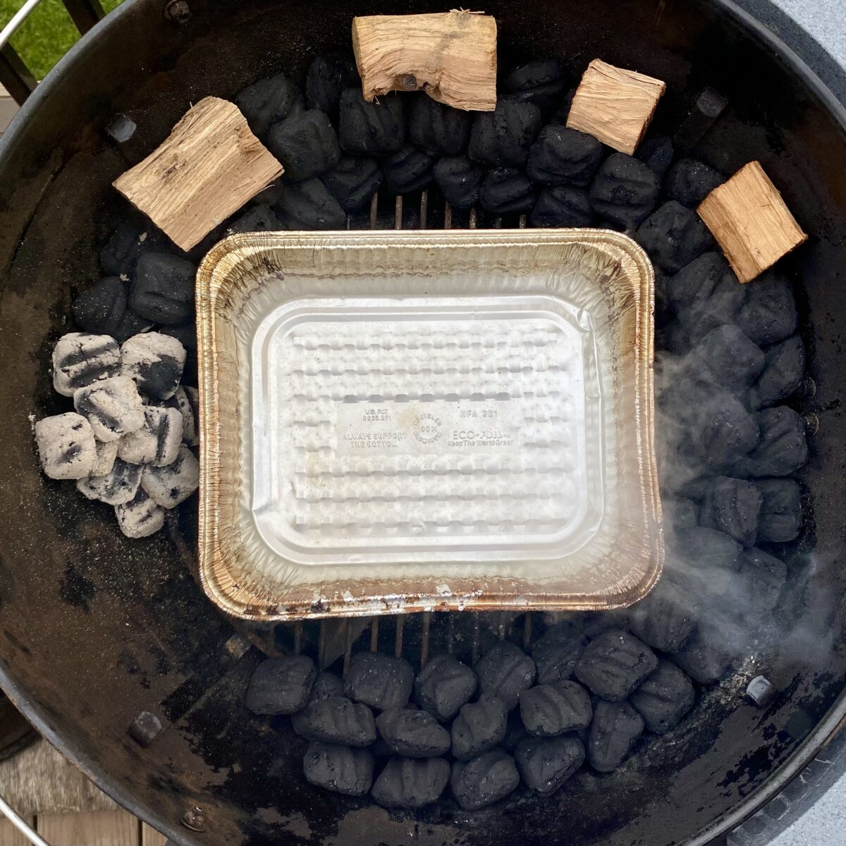 Overhead view showing water pan filled with boiling water in the middle of snake of coals that have just been lit.