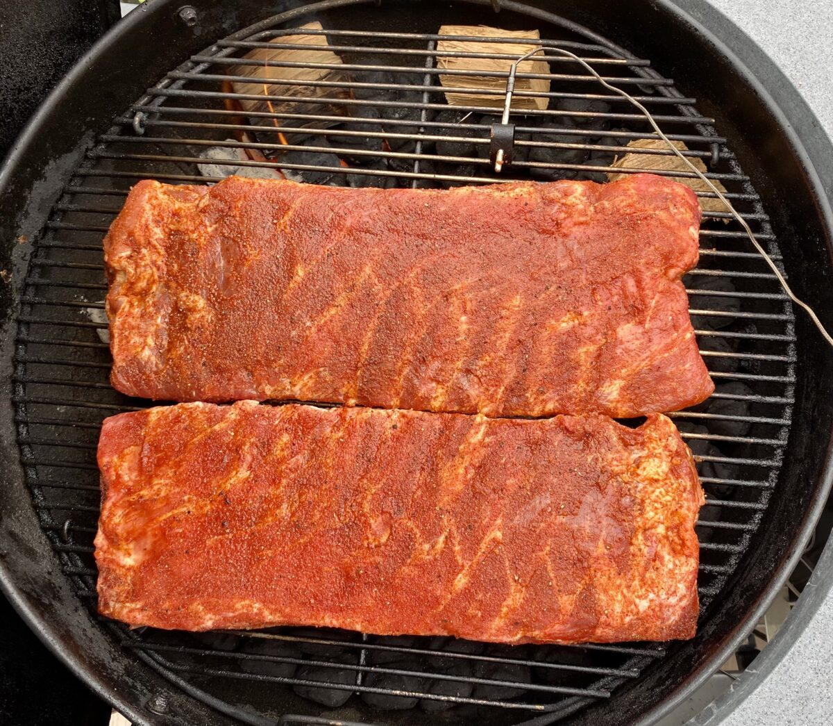 Overhead view showing where to position two racks St Louis spare ribs  that are to be smoked on a charcoal grill.