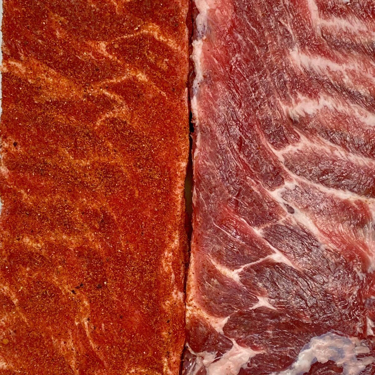 Overhead close up view of two racks of ribs side by side.  One on the left rubbed down with rib rub, the one on the right, not rubbed yet.