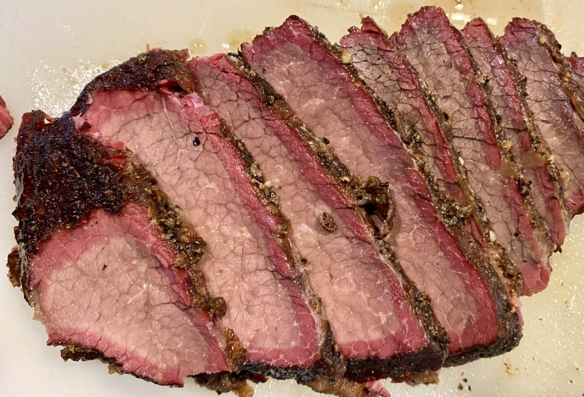 Top view of sliced smoked brisket on a cutting board clearly showing the smoke ring.