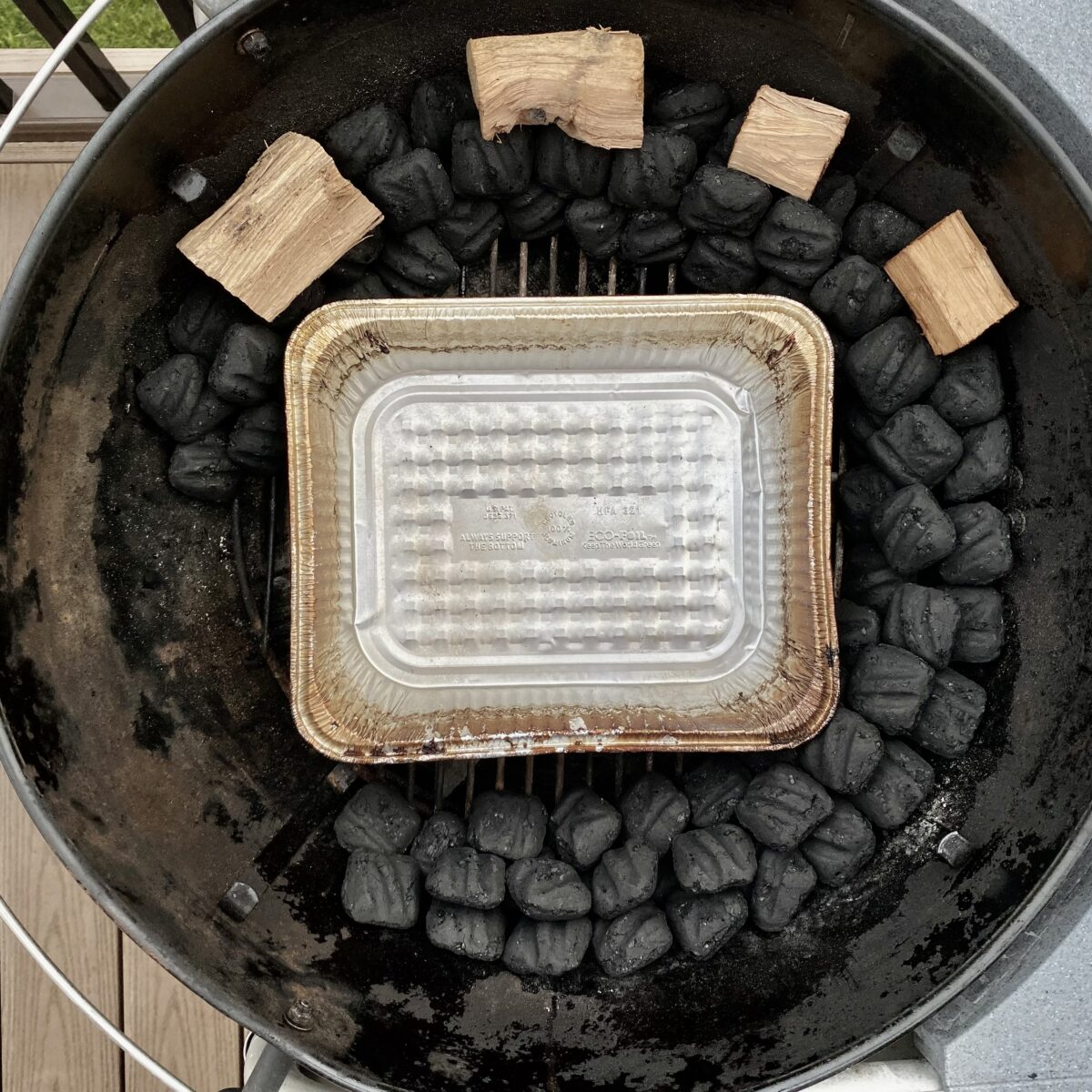 Overhead view showing the water pan placement in the middle of the snake of unlit coals.