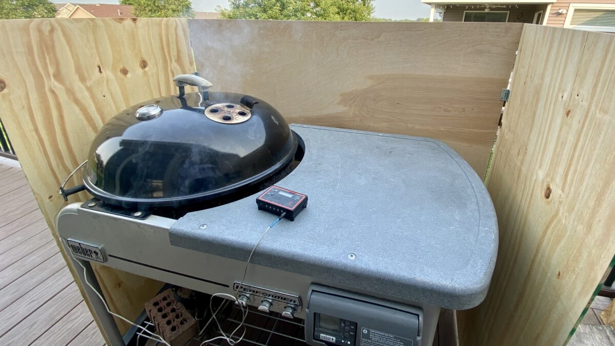 Side view of charcoal grill positioned inside of a homemade wind shield which consists of 3 pieces of plywood connected to each other with hinges.
