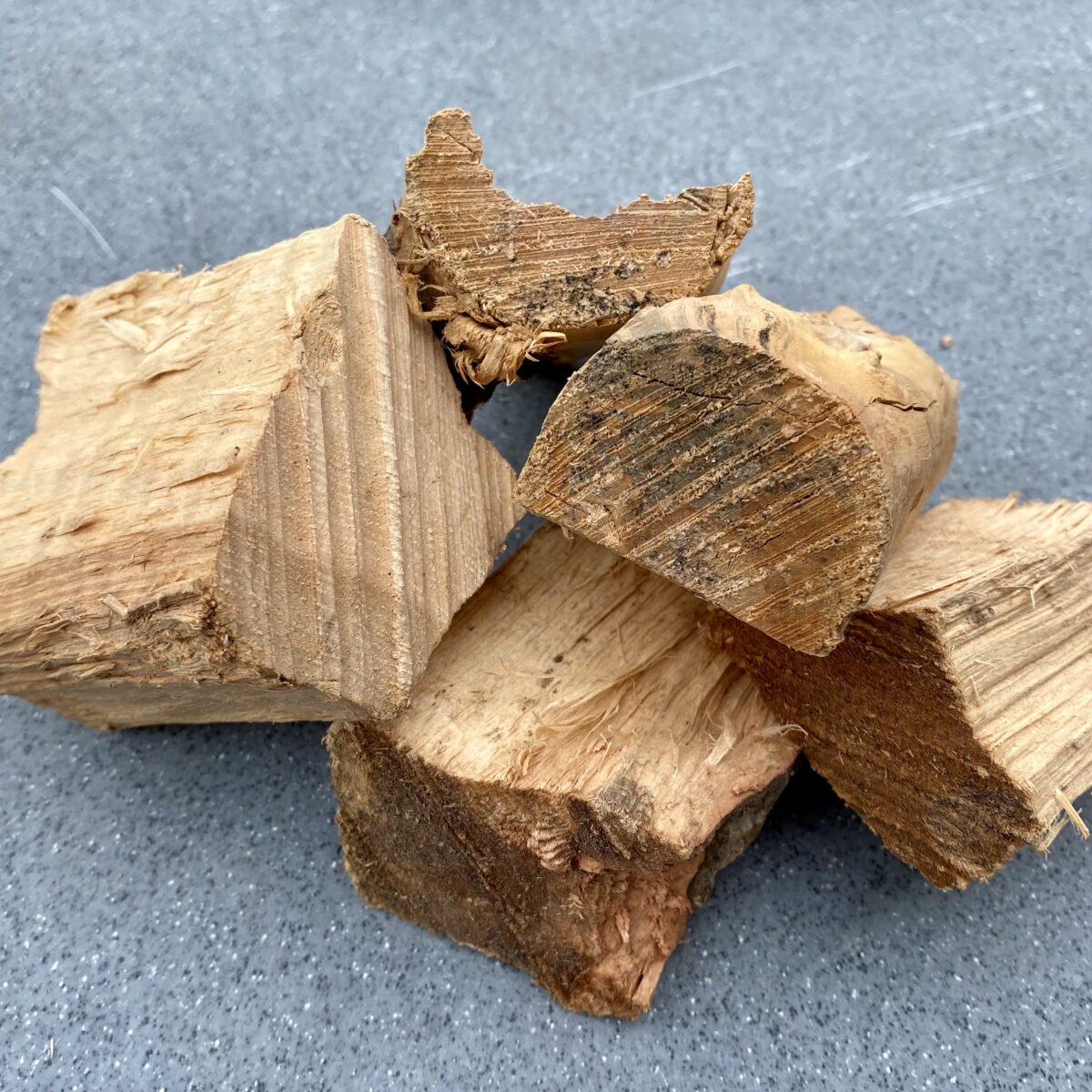 Five pieces of smoke wood chunks stacked on each other showing the size of one to two inches for each piece.