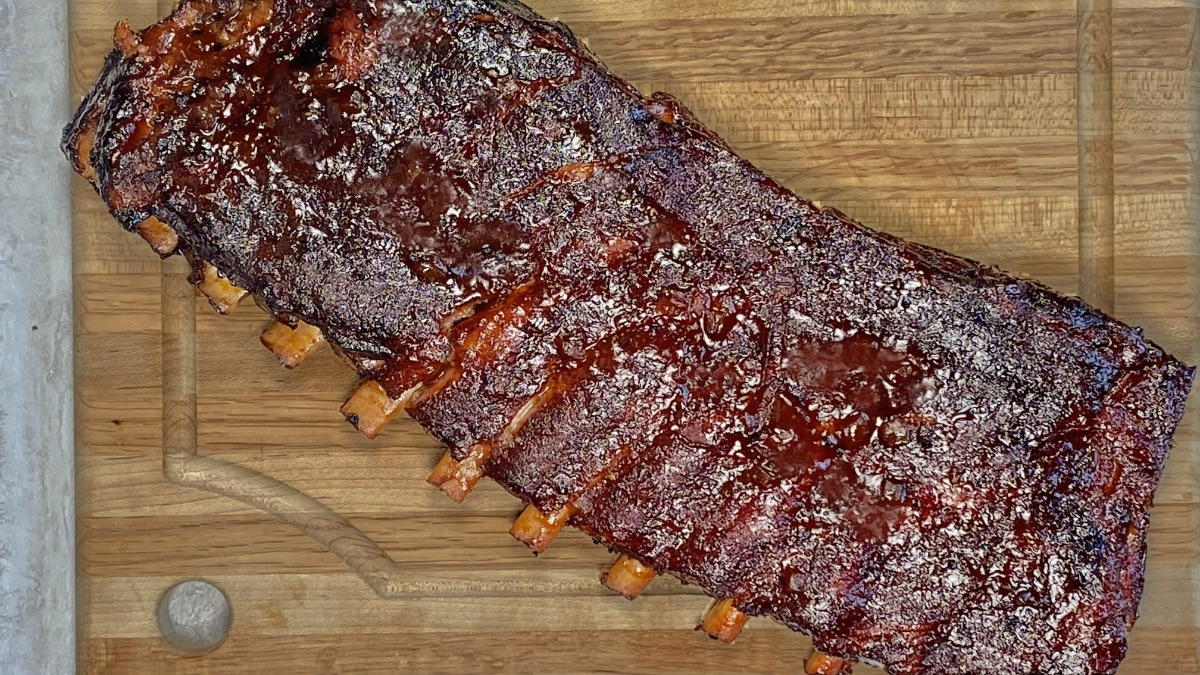 A rack of St. Louis ribs smoked on a charcoal grill, with meat pulling back nicely from the bone.