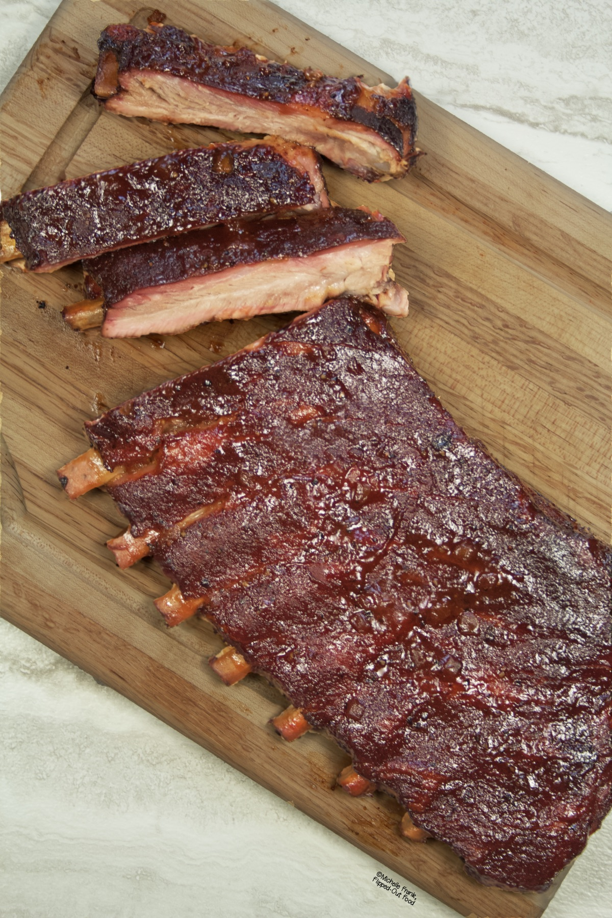 Side view of a partially cut rack of ribs that have been smoked on a charcoal grill, positioned on a cutting board