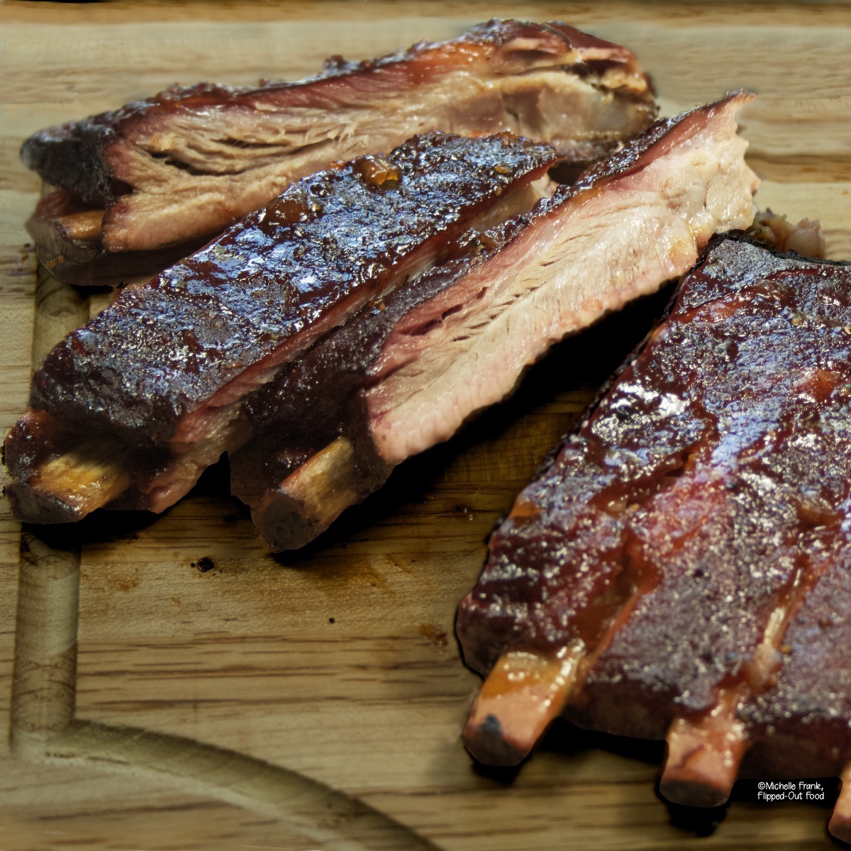 Close up side view of 3 ribs from a rack of ribs on a cutting board which shows the smoke ring and how juicy they look.