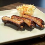 Three perfectly smoked ribs, fresh off the charcoal grill, served with coleslaw.