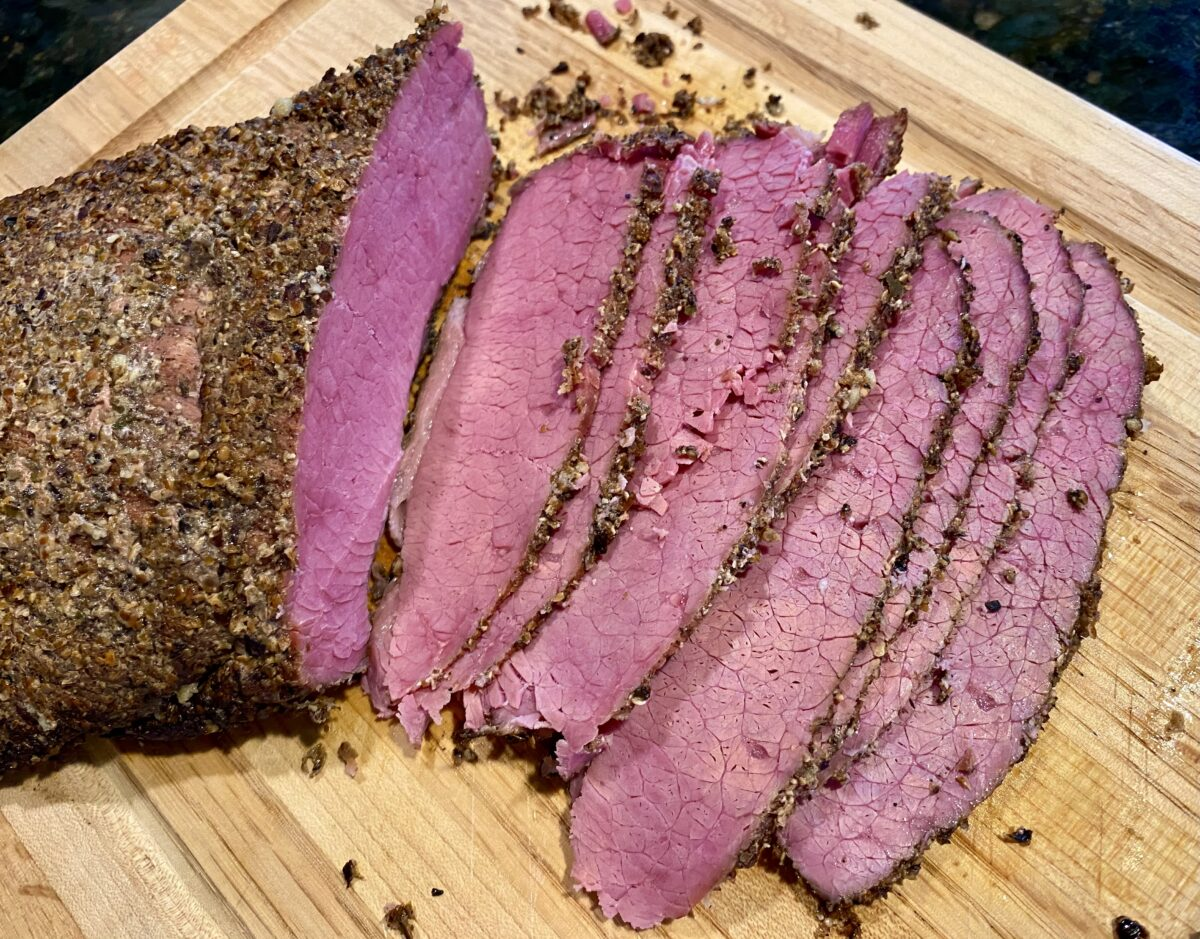 Top view of sliced corned beef smoked on a charcoal grill positioned on a wooden cutting board.