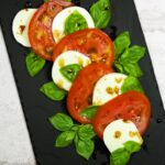A whimsically arranged Caprese Salad with Balsamic Glaze on a slate platter.