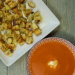 A plate of freshly made Easy Stovetop Croutons on a white plate sitting next to a bowl of fresh tomato soup.