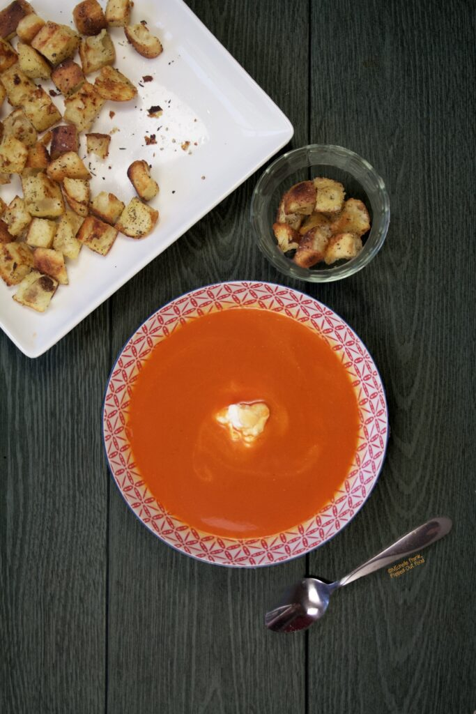 A bowl of Fresh tomato soup with a dollop of ricotta, sitting next to a platter and a ramekin with freshly made stovetop croutons.