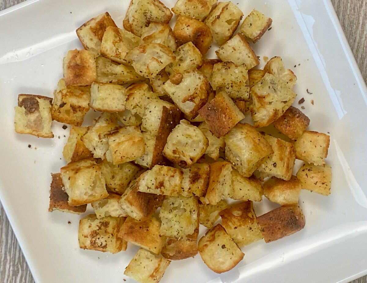 Overhead view of freshly made stovetop croutons in a white square platter.